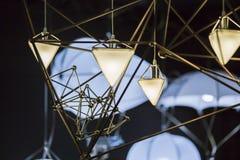 Modern ljuskrona i form av en triangel och metalliska geometriska former, på en svart bakgrund Royaltyfri Bild