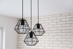 A modern loft chandelier made of black wire in a stylish white interior Stock Photos