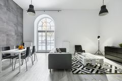 Modern loft interior. With sofa, dining table with chairs, studio lamp and big window stock photography