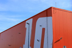 Modern logistics warehouse exterior. Industrial warehouse with orange and white number on the surface stock images