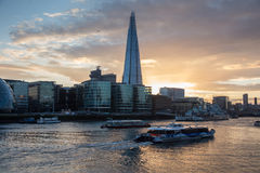 Modern London cityscape at sunset. The Shard and office buildings in modern London skyline, at sunset in London, UK. Cruise boats on Thames river Stock Image