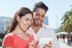 Modern love couple looking photos on cell phone. Wit modern buildings in the background Stock Photos