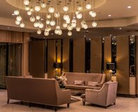 Modern luxurious lobby for hotel with comfortable sofas, arm chairs and moody lighting. Idea for luxurious lobby for five star hotel with comfortable sofas, arm royalty free stock photos