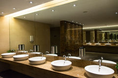Modern Luxurious Washroom. Row of wash basin with marble counter and mirror reflection Stock Images