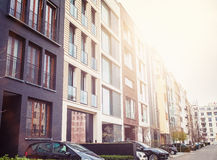 Modern luxury apartment buildings on street. Neighborhood of luxury residential apartment buildings with parked cars on street with copy space royalty free stock image