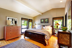 Modern luxury bedroom with bed, dresser and nightstand. Vaulted ceiling Royalty Free Stock Image