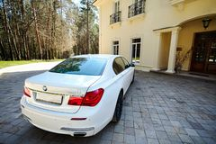 Modern luxury BMW 750Li XDrive car rear back upper view parked on stone paved parking near ancient house stock photos