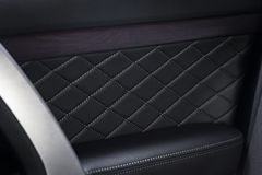 Part of  leather car door panel details. Modern luxury car  black leather interior. Part of   leather details. Car door wood panels Stock Images