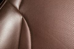 Modern luxury Car brown leather interior. Part of leather car seat details with white stitching. Interior of prestige car. Comfort. Able perforated leather seats stock photography