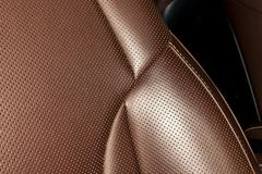 Modern luxury Car brown leather interior. Part of leather car seat details with white stitching. Interior of prestige car. Comfort royalty free stock photo