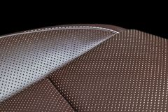 Modern luxury car brown leather interior. Part of leather car seat details with white stitching. Interior of prestige car. Comfort. Able perforated leather seats royalty free stock images