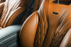 Modern Luxury car inside. Interior of prestige modern car. Comfortable leather red seats. Orange perforated leather cockpit with i. Modern Luxury car inside Stock Image
