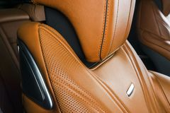 Modern Luxury car inside. Interior of prestige modern car. Comfortable leather red seats. Orange perforated leather. Modern car. Interior details Stock Photo