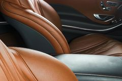 Modern Luxury car inside. Interior of prestige modern car. Comfortable leather red seats. Orange perforated leather. Modern car in. Terior details Stock Photo