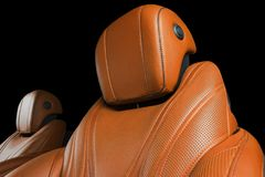 Modern Luxury car inside. Interior of prestige modern car. Comfortable leather seats. Orange perforated leather cockpit. With isolated Black background. Modern Stock Photography
