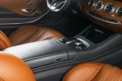 Modern Luxury car inside. Interior of prestige modern car. Comfortable leather seats. Orange perforated leather cockpit. Steering. Wheel and dashboard Royalty Free Stock Photo