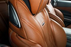 Modern Luxury car inside. Interior of prestige modern car. Comfortable leather red seats. Orange perforated leather cockpit with. Black background. Modern car Stock Photography