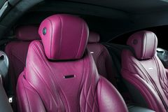 Modern Luxury car inside. Interior of prestige modern car. Comfortable leather red seats. Pink perforated leather cockpit. With  Black background. Modern car Stock Images