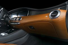 Modern Luxury car inside. Interior of prestige modern car. Comfortable leather seats. Orange perforated leather cockpit. Steering. Wheel and dashboard Royalty Free Stock Images