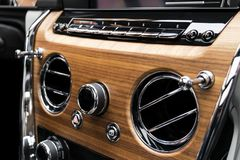 Modern Luxury car inside. Interior of a vehicle with natural wood panel. White Leather with stitching. Car detailing. Dashboard. M royalty free stock image
