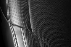 Modern luxury car leather interior. Part of leather car seat details with white stitching. Interior of prestige car. Comfortable p. Erforated leather seats royalty free stock photos