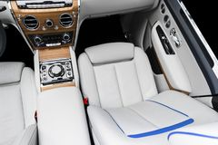 Modern luxury car white leather interior with natural wood panel. Part of leather car seat details with stitching. Interior of pre royalty free stock photography