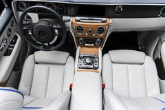 Modern luxury car white leather interior with natural wood panel. Part of leather car seat details with stitching. Interior of pre stock image