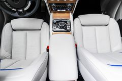 Modern luxury car white leather interior with natural wood panel. Part of leather car seat details with stitching. Interior of pre royalty free stock photos