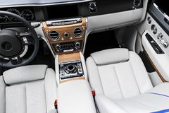 Modern luxury car white leather interior with natural wood panel. Part of leather car seat details with stitching. Interior of pre stock images