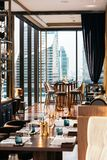 Modern luxury decorated interior restaurant that can view Bangkok cityscape. Elegant design for fine dining.  royalty free stock image