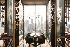 Modern luxury decorated interior restaurant that can view Bangkok cityscape. Elegant design for fine dining.  stock photos