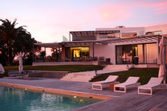 Modern Luxury house pool at sunset Royalty Free Stock Photos