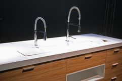 Modern luxury kitchen. Modern luxury kitchan with chrom faucet and wooden arms Royalty Free Stock Images