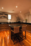 Modern luxury kitchen with seats in foreground Royalty Free Stock Images
