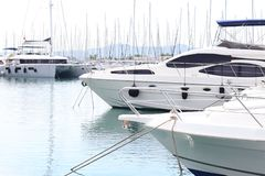 Modern luxury motor cruise yachts on the quay in the marina. Leisure activities of rich people at sea. Water transport for royalty free stock photography