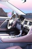 Modern luxury prestige car interior, dashboard, steering wheel. Sunrise in the windows Royalty Free Stock Image