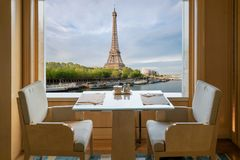 Modern luxury restaurant interior with romantic sence Eiffel Tow. Er and Seine river view in Paris, France. Dinning table in restaurant at Paris, France stock image