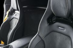 Modern Luxury sport car inside. Interior of prestige car. Leather seats with yellow stitching. Black perforated leather. Modern. Car interior details Stock Images