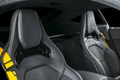 Modern Luxury sport car inside. Interior of prestige modern car. Comfortable leather seats with yellow stitching. Black perforated. Leather. Modern car interior Stock Images