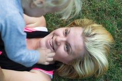 Modern lyftte över hennes barn som ler och ligger på gräs Royaltyfri Foto