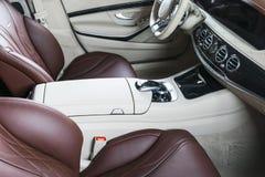 Modern lyxig bil inom Inre av den moderna bilen för prestige Bekväma läderplatser Röd och vit perforerad lädercockpit Royaltyfri Fotografi