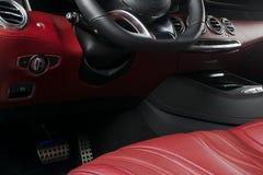 Modern lyxig bil inom Inre av den moderna bilen för prestige Bekväma läderplatser Röd perforerad lädercockpit styrning Arkivfoton