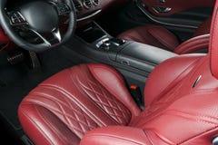 Modern lyxig bil inom Inre av den moderna bilen för prestige Bekväma läderplatser Röd perforerad lädercockpit styrning Arkivbild