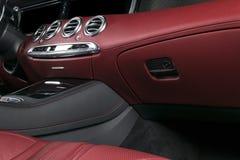Modern lyxig bil inom Inre av den moderna bilen för prestige Bekväma läderplatser Röd perforerad lädercockpit styrning Arkivfoto