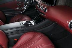 Modern lyxig bil inom Inre av den moderna bilen för prestige Bekväma läderplatser Röd perforerad lädercockpit styrning Royaltyfri Foto