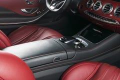 Modern lyxig bil inom Inre av den moderna bilen för prestige Bekväma läderplatser Röd perforerad lädercockpit styrning Royaltyfri Bild