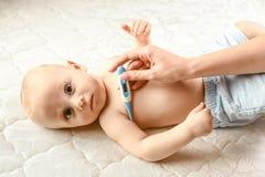 Modern mäter temperaturen av dåligt ett barn moderlig omsorg för behandla som ett barn royaltyfri bild