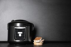 Modern mång- spis och skivat bröd på tabellen nära den mörka väggen arkivfoton