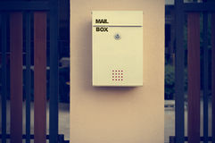 Modern mail box on concrete wall and wooden fence, vintage color Royalty Free Stock Images