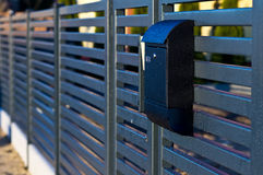 Modern mailbox. Covered with rain droplets, lit by sunset light stock photography